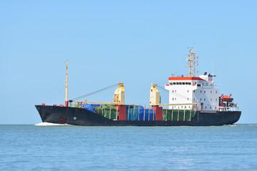 Cargo ship sailing in blue sea to the port of Antwerpen, Belgium