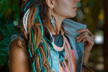close up photo of hippie girl wearing denim jacket with dreadloc