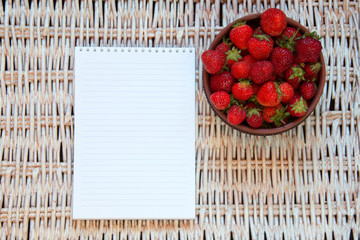 fresh strawberries in brown plate with paper notebook on braided