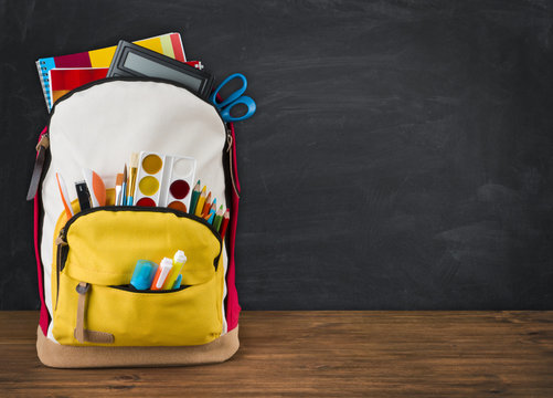 Backpack full of school supplies over black school board background