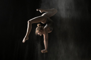 Gymnastic flexible woman handstand on equilibr at sprinkled flour