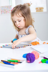 girl playing with colored plasticine