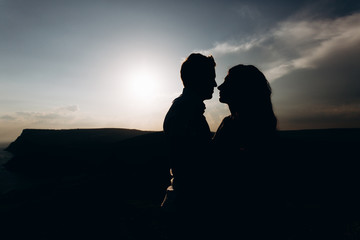 silhouette guy and girl in the mountains