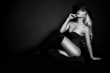 Beautiful blond woman girl sexy model dressed in black lingerie outfit body swimsuit and black hat and long boots knee