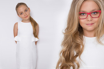 Portrait of a lovely little girl daughter in long blond hair and white dress and red glasses with white dots looks at the camera, photo on the white background amazing eyes