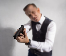 Solid man with a gun in his hand, shoot against a white wall