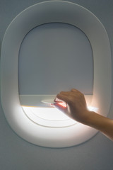 Hand pulling down aircraft window curtain