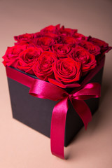 box with red roses over beige background