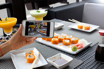 Woman photographing food served in sushi bar with mobile phone.
