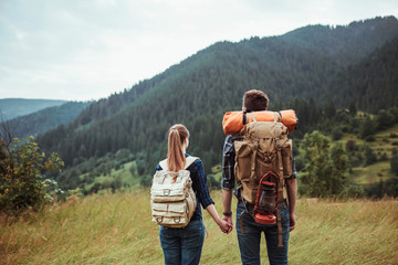 A couple hikers Hiking with backpacks walk along a beautiful mountain area holding hands . The concept of active rest