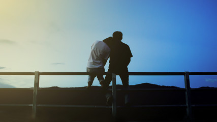 silhouette couple sitting on the iron fence with love with sunlight, soft focused