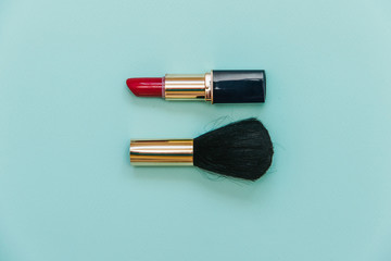 Flat lay fashion set: red lipstick and brush for powder on pastel background.
