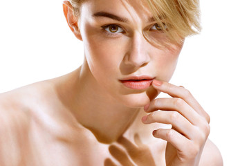 Sensual blonde girl touching her lips. Close up of an attractive girl of European appearance on white background. Youth and Skin Care Concept.