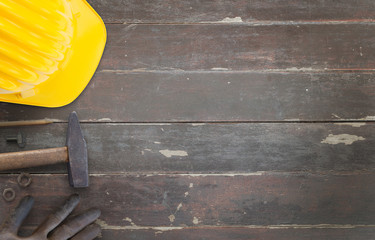 Helmet, hammer, gloves and pencil on wooden desk. Construction site.