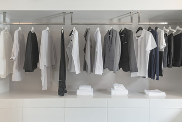 black and white color tone clothes hanging on rail