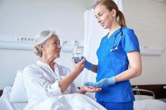 nurse giving medicine to senior woman at hospital