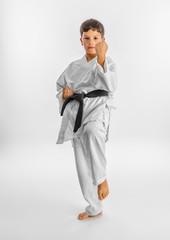 Boy in white kimono during training karate kata exercises