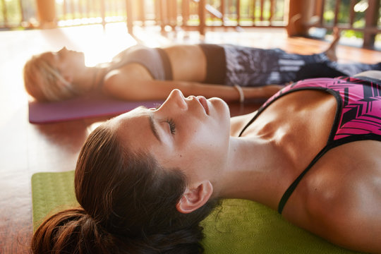 Young people relaxing in savasana pose at yoga class