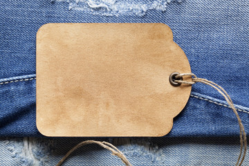 Blank paper label on jeans background