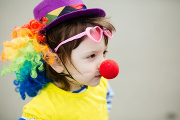 Adorable little girl in clown costume outdoors at summer day