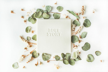 """white wedding or family photo album with words """"love story"""", frame with dry and fresh branches isolated on white background. flat lay, overhead view"""