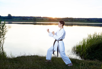 Young girl on the water background is in the rack karate