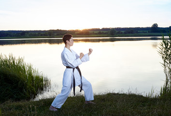 Girl in white kimono in rack karate on the background of the river