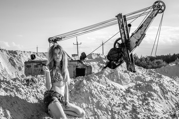 Young bewitching sexy girl with long beautiful hair in denim shorts and a bikini bathing suit sitting on a mountain of sand in the sand pit, the background industrial excavator bucket sand mining its