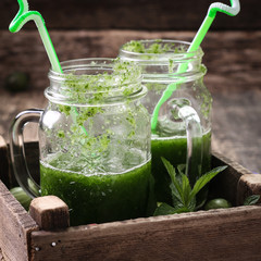 Fresh green smoothie with straws on a wooden table,healthy vegan food
