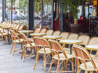 PARIS, FRANCE, on JULY 12, 2016. Little tables of typical Parisian cafe on the sidewalk near big window.