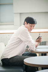 asian man. businessman looking on mobile phone in modern office