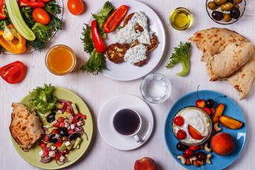 Greek appetizers  - fritters of zucchini, Greek salad, yogurt.