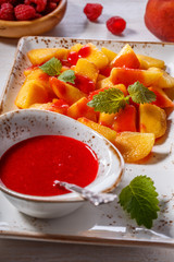 Plate of Sliced Peaches with Raspberry Sauce and Mint Leaf.