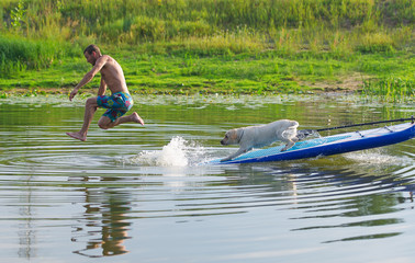 The young man and dog in the boat. The  jumps from the  in water.