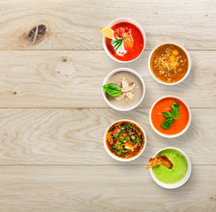 Six soups at wood, top view with copy space