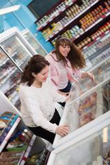 Women looking in display with frozen food