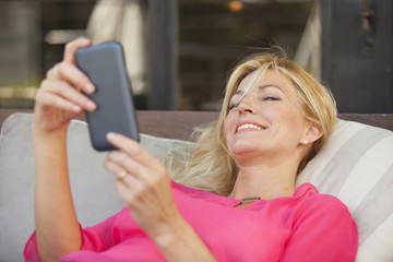 Happy adult blonde woman smiling with mobile phone