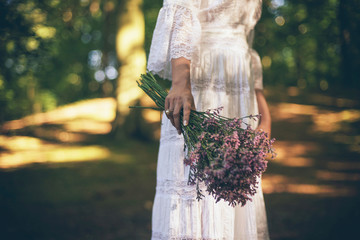 Hand of bride holding purple flowers