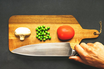 Fresh products are neatly on a wooden cutting board and woman hand with a bid kitchen knife