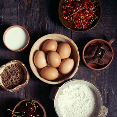 Ingredients for fruit and chocolate cake in rustic kitchen; sele
