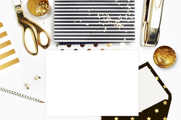 Flat lay, office white desk and envelope with gold stationery. Gold stapler, stripe gold pattern, pencil. View top. Table up. Mock-up background