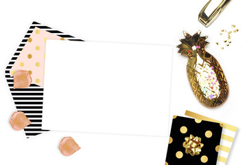 White background with an invitation envelope. Gold woman items on table.Top view, glamour style. Flat lay, party desk. Table view, workspace. Pineapple. Polka pattern