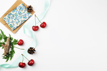 White desk, envelope and cherry, invitation. Flat lay. Party