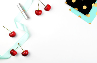 Flat lay. White desktop, cherry and lipstick on the table. Gold polka pattern black and blue.