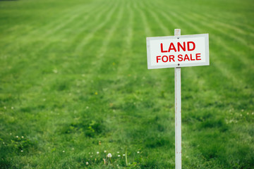 land for sale sign against trimmed lawn background Wall mural