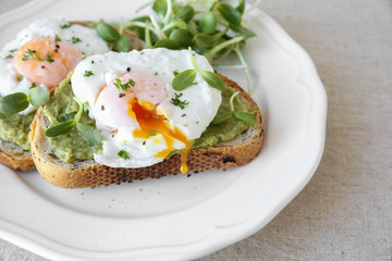 Poached eggs with avocado and sunflower sprout on sourdough toas