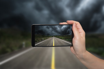 Mobile phone in hand and storm landscape