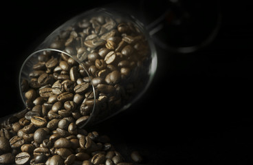 Coffee beans in wineglass on black background