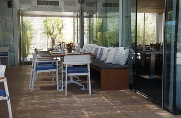 Summer cafe with white furniture and glassy walls view from within