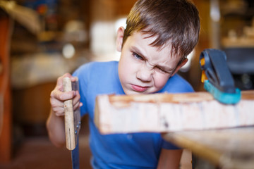 child does handicraft. boy trying on a block of wood order to saw off part